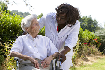 Afro-american caregiver talking to disabled senior woman outdoors