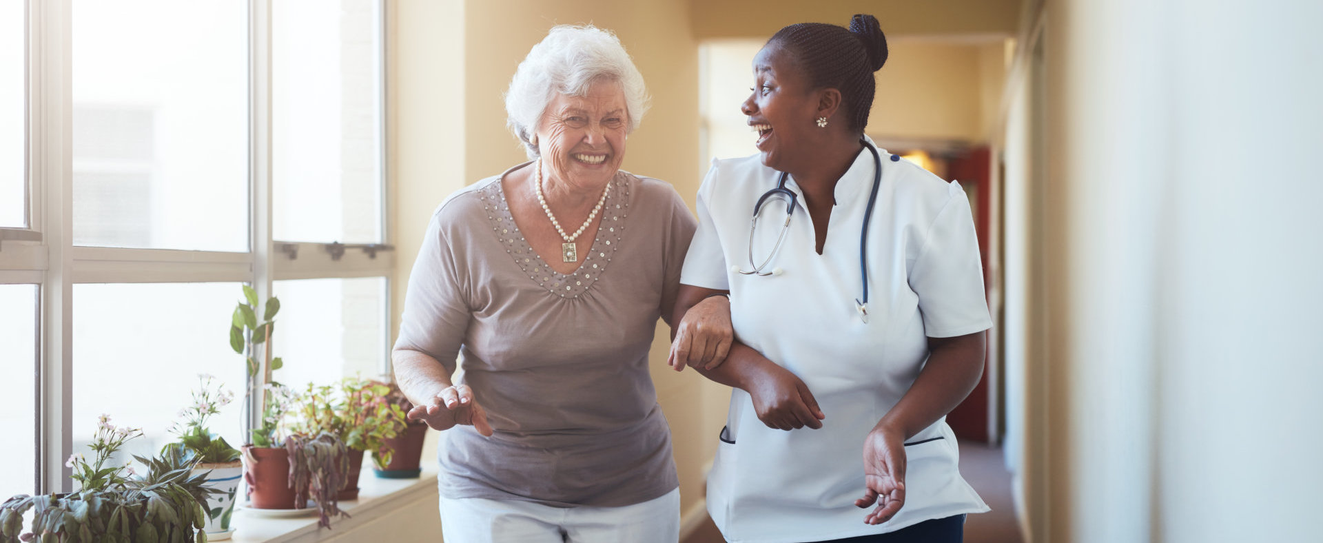 Portrait of happy healthcare worker and senior women walking together