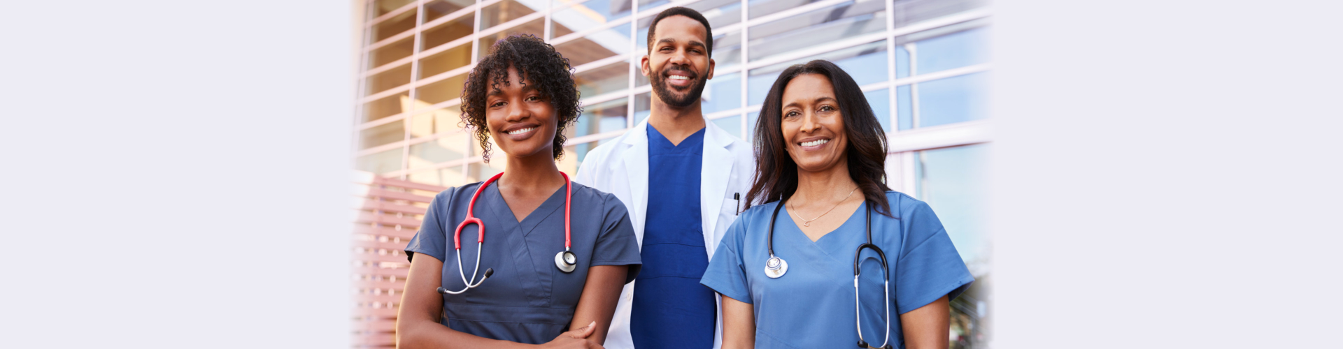 Three healthcare colleagues standing outside modern hospital